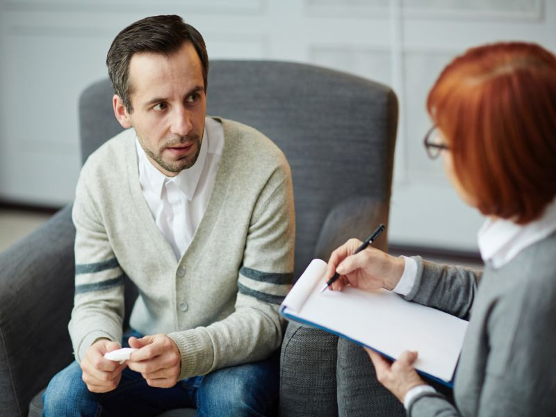 Depressed middle-aged patient sitting nervously on comfortable armchair with handkerchief in hands and explaining his problems to mature psychologist with clipboard and pen
